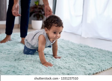 Baby boy crawling on rug carpet with mother parent in background helping, involved parenting