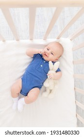 a baby boy in a crib lies on his back, a happy newborn wakes up in the morning or goes to bed