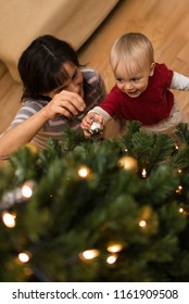 Baby boy decorating christmas tree alongwith her mother