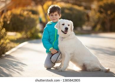 baby boy with a dog breed Golden Retriever on a walk best friends