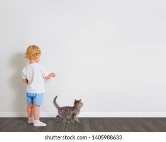 Baby boy drawing on wallpaper standing back to camera with little cat