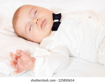 Baby boy dressed for party sleeping peacefully.