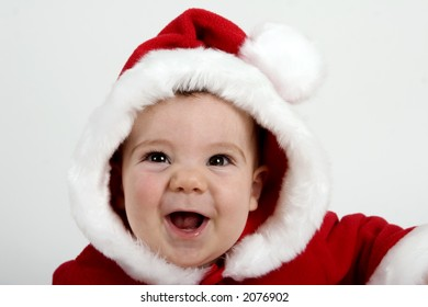 Baby boy dressed in red Santa coat and hood trimmed in white fur.