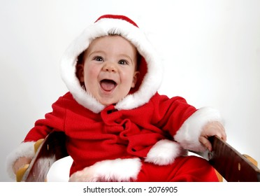 Baby boy dressed in red Santa coat and hood trimmed in white fur, sitting on a sled