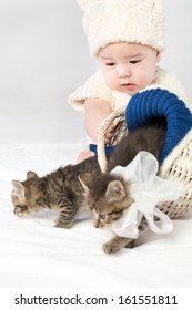 Baby boy dressed in white fur lets out from a basket two small kittens