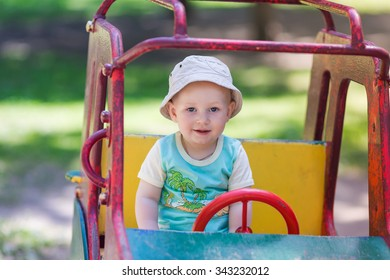 Baby boy driving a toy car at the playground outdoor