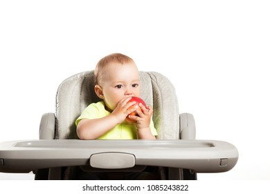 baby boy eating a big red apple, on white background.