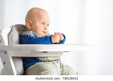 Baby boy eating bread and cucumber with BLW method, baby led weaning. Vegetarian  kid eating lunch.