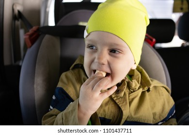 Baby boy eating corn sticks in the car