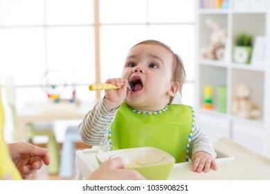 baby boy eating food in nursery at home