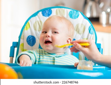 baby boy eating food on kitchen at home
