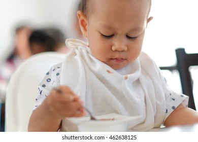 baby boy eating ice cream and Playing smartphone in Ice cream shop
