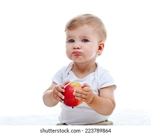 Baby boy eating a red apple - isolated