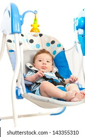 Baby boy in electrical swing isolated on white background