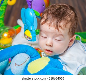 Baby boy falling asleep while playing on the playmat.