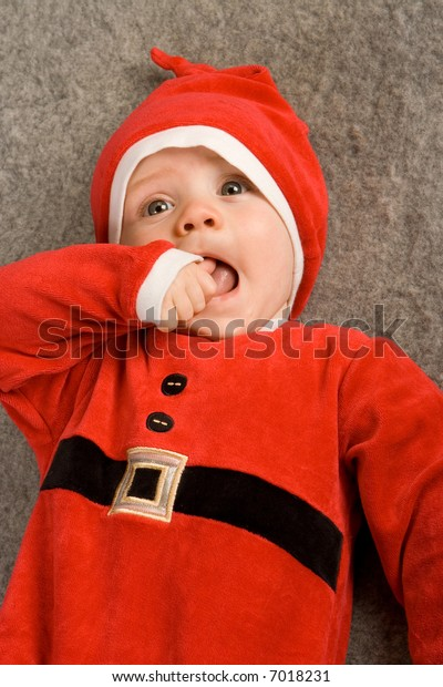 Baby boy in Father Christmas outfit laying on a grey fleecy mat, looking surprised and putting his thumb in his mouth