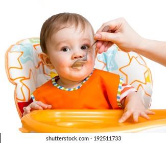 baby boy feeding with a spoon