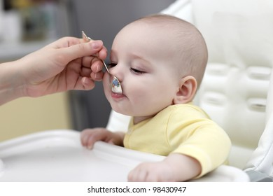 The baby boy feeding with spoon at home