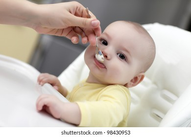 The baby boy feeding from a spoon at home