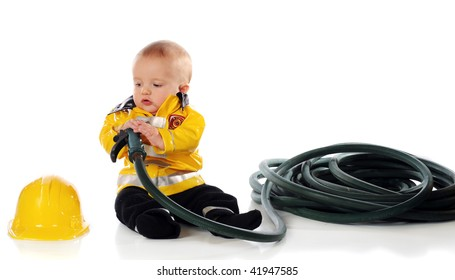 A baby boy in a fireman's suit, eying his hat while holding the nozzle and hose.
