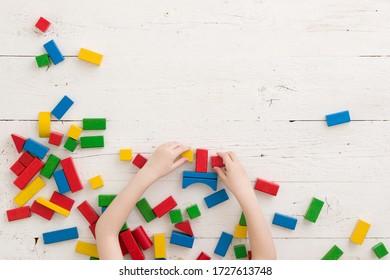 Un petit garçon ou une petite fille joue avec des briques colorées sur une table blanche en bois. Vue en haut sur des briques en bois colorées sur fond de bois. Concept d'école, d'éducation et d'apprentissage.