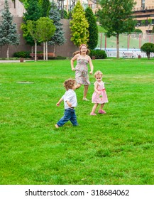 Baby boy and baby girl playing with their older sister in the park.