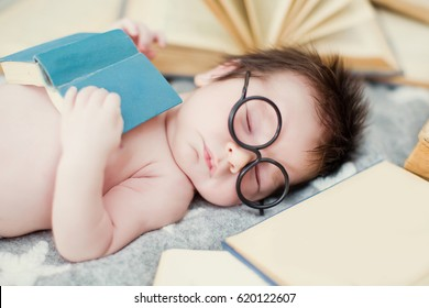 baby boy in glasses with books