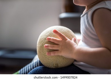 baby boy hands hold and touch raw fresh yellow melon indoor. baby exploring fruits