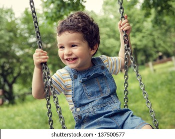 Baby boy having fun on a swing.