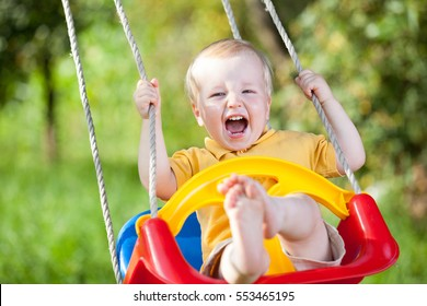 Baby boy having fun on a swing in summer day