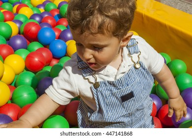 Baby boy having fun playing in a colorful plastic ball pool in a playground