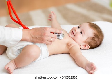 Baby boy having it's heartbeat checked by doctor pediatrist