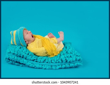 Baby boy is having his first photo shoot and he is yawning. He is dressed in yellow and blue clothes and is wearing a hat in the same colours.
