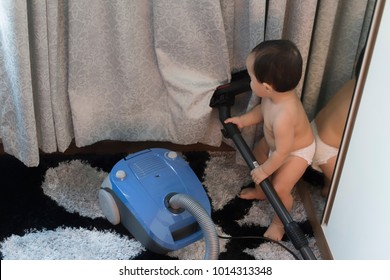 A baby boy is helping on household chore. A baby boy is using home cleaning equipments. Spring Cleaning Ideas.
