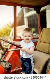 Baby boy holding a steering wheel of tractor. Childhood moments on the countryside.