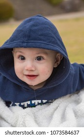 Baby boy in hoodie with big eyes at the park.