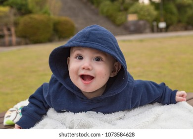 Baby boy in hoodie smiling at park.