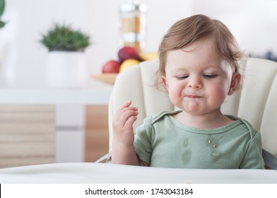 Baby boy with index finger in his mouth while eating a buiscuit