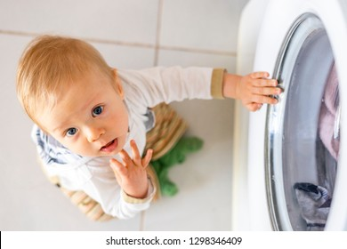 Baby boy interested in the cycles of washing machine doing laundry