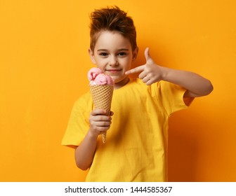 Baby boy kid eating strawberry ice-cream in waffles cone happy pointing finger show thumbs up on yellow background with free text copy space