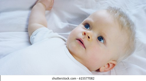 A baby, a boy with large blue eyes and light colored hair, lies and smiles on a snow white blanket, looks at her mother, on a white background. Concept: children, kids, baby, babies, a new generation.