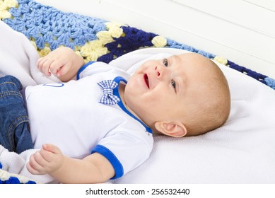 Baby boy laughing lying on blanket