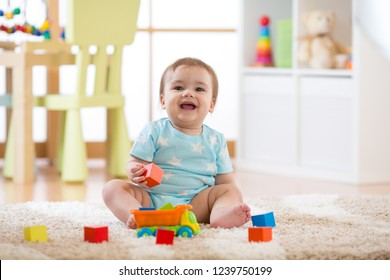 Baby boy laughing and playing with colorful toys sitting on soft carpet in nursery