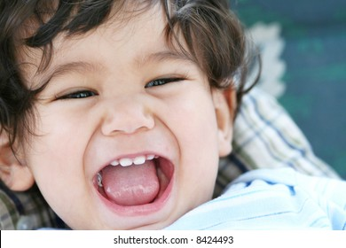 Baby boy laughing and smiling with mouth wide open.