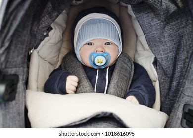 baby boy laying in the gray stroller