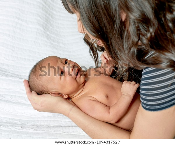 Baby boy laying on white blanket with mother's hands on his head looking at him as he is starting to cry