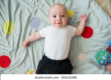 baby boy lays on back on playmat and looks up at camera