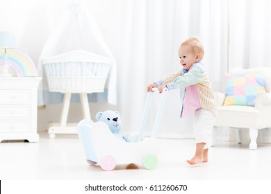 Baby boy learning to walk with wooden push walker in white bedroom with pastel rainbow color toys. Aid toy for child first steps. Toddler kid walking with car wagon. Nursery interior for baby