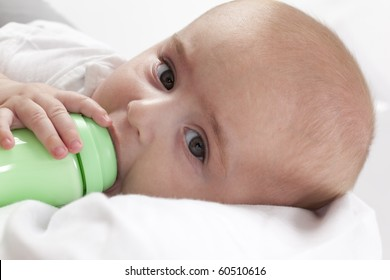 Baby boy looking into the camera while drinking from a baby bottle on white background
