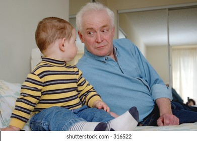 Baby boy is looking at old men. Focused on the boy, men is in soft focus.